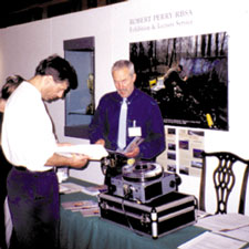 """Rob Perry taking bookings at the """"Touring Exhibition Group"""" marketplace."""