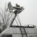 Robert Perry sitting aloft on the van rooftop painting rig. Photo